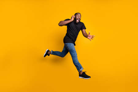 Wait i hurry. Full body profile side photo of crazy funny afro american guy jump speak cellphone run buy black friday discounts wear t-shirt denim jeans isolated yellow color background