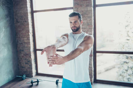 Photo of macho guy preparing to morning training stretch hand fingers muscles sportswear tank-top shorts sneakers training house studio big windows indoors