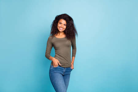 Portrait of charming pretty content afro american have fun on weekends enjoy holidays put hands in pockets good-looking outfit isolated over blue color background