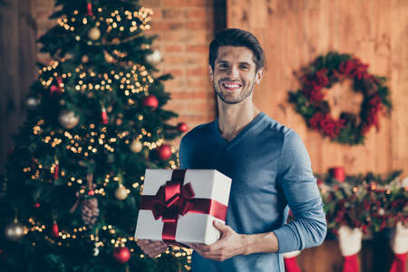 Photo of cheerful positive handsome man smiling toothily holding wrapped gift box present from santa claus standing in front of christmas tree