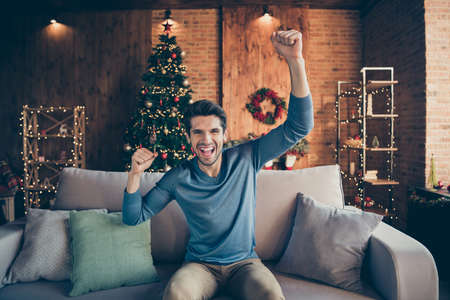 Portrait of crazy funky guy have rest on christmas day watch dream soccer match playing support team scream yeah in house with x-mas lights ornaments Stock Photo