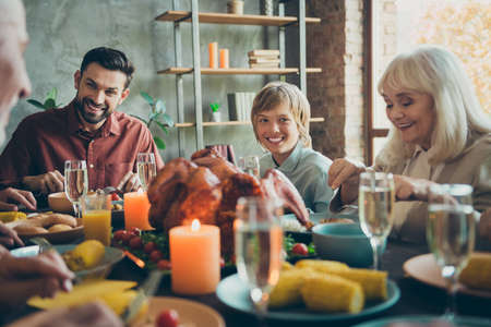 Big happy family little small boy pensioner sit table enjoy october thanksgiving party celebration have large feasting banquet with wine corns vegetables meat chicken candles in house indoors Stock fotó
