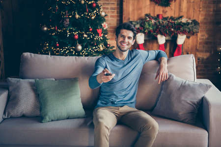 Portrait of positive guy sit couch watch tv christmas films switch channels enjoy newyear atmosphere spirit in house with noel decoration evergreen tree red stockings