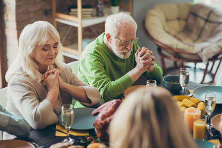 Grandparents charming couple gathering sit table celebrate thanksgiving day pray with family relatives have banquet in house indoors
