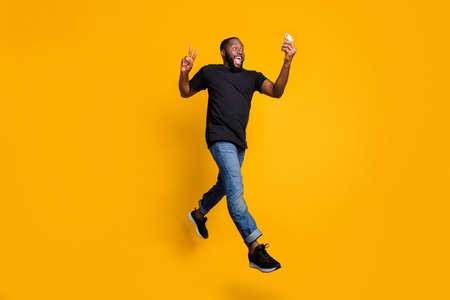 Full size photo of funny crazy afro american guy have journey make v-sign selfie go walk record video smartphone jump wear t-shirt denim jeans isolated yellow color background