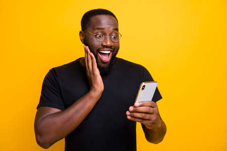 Photo of ecstatic overjoyed man browsing through his telephone rejoicing in receiving, positive notifications in t-shirt isolated vivid color yellow background
