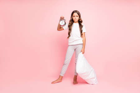 Full length body size view of her she nice attractive cute lovely disappointed irritated wavy-haired pre-teen girl carrying holding in hands pillow bell clock isolated on pink pastel color background