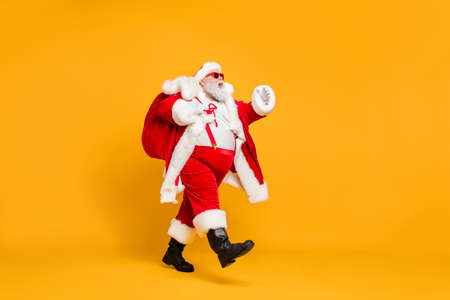 Full size profile side photo of funky fat santa claus with huge abdomen hold gift wish bag go walk travel around world on christmas night eve wear x-mas hat suspenders isolated bright color background Stock Photo