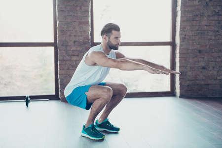 Full body profile photo of macho guy doing static squats fat burning process sportswear tank-top shorts sneakers training house home studio near big windows indoors Banco de Imagens