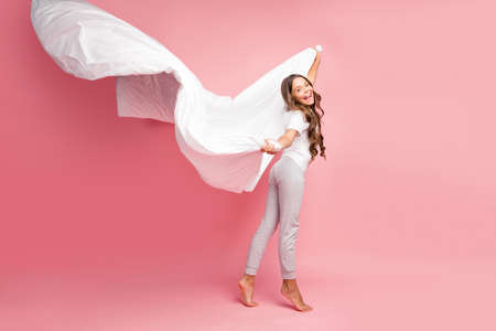 Full length body size view of nice attractive lovely cute cheerful funky funny wavy-haired pre-teen girl wind blowing veil new cotton house domestic collection isolated on pink pastel color background