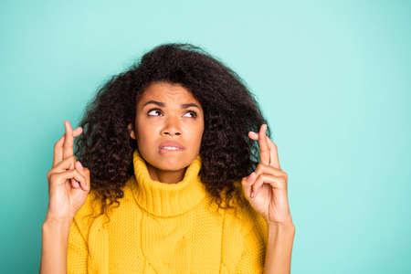 Primo piano di un'incredibile signora dalla pelle scura che tiene le dita incrociate che mordono le labbra preoccupata per il test scolastico indossa un maglione lavorato a maglia giallo isolato blu verde acqua di sfondo di colore