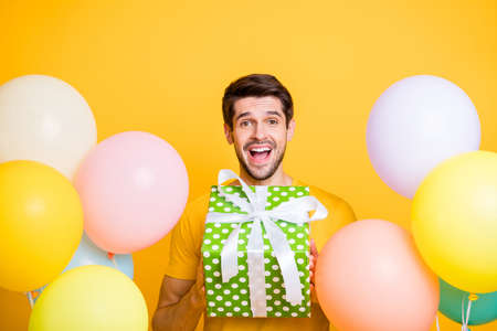 Photo of handsome friendly guy between many air balloons holding big giftbox amazed birthday surprise wear casual t-shirt isolated yellow color background