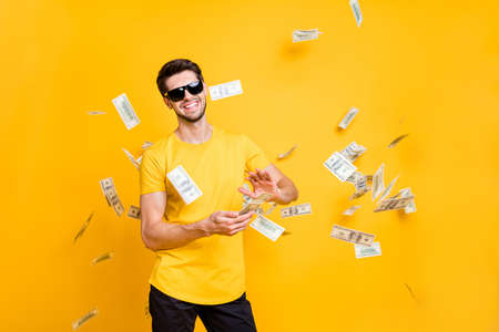Photo of young handsome careless guy throwing usa money banknotes away wealthy person wear sun specs casual t-shirt isolated bright yellow color background Фото со стока