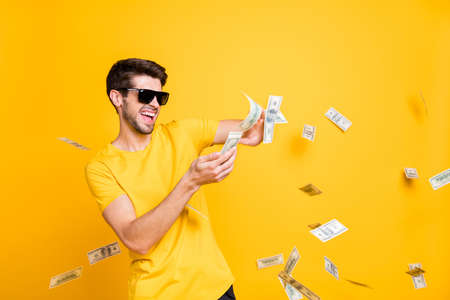 Photo of handsome careless generous guy throwing money banknotes away wealthy person wear sun specs casual t-shirt isolated bright yellow color background