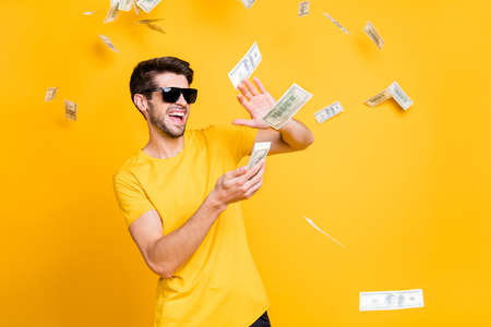 Photo of young handsome careless guy throwing money banknotes away wealthy person wear sun specs casual t-shirt isolated bright yellow color background