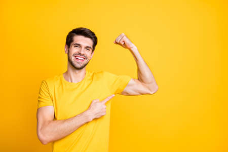 Photo of young handsome guy holding fist raised demonstrating perfect big biceps indicating finger on muscle wear casual t-shirt isolated yellow color background