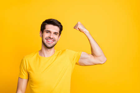 Close-up portrait of his he nice attractive content sportive cheerful cheery guy demonstrating muscles motivation isolated over bright vivid shine vibrant yellow color background