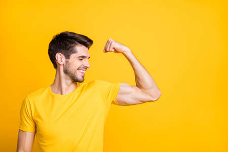 Photo of young handsome guy holding fist raised demonstrating perfect big biceps result after new sport gym wear casual t-shirt isolated yellow color background Stock fotó