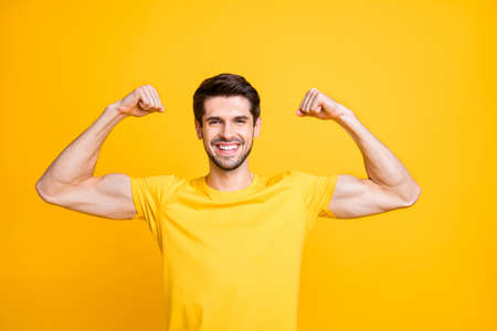 Photo of young handsome guy holding fists raised demonstrating perfect big biceps result after new sport gym wear casual t-shirt isolated yellow color background