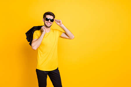 Photo of handsome guy holding boutique bags making abroad shopping self-confident classy person wear casual t-shirt pants isolated yellow color background