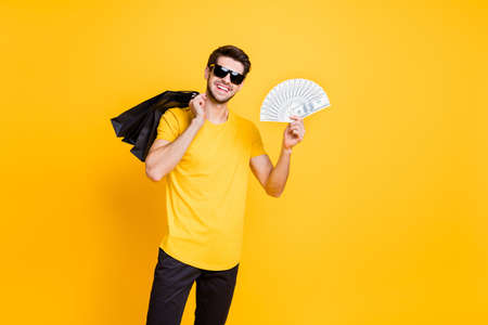I will pay for it. Photo of handsome guy holding boutique bags making abroad shopping, showing fan of usa bucks wear casual t-shirt pants isolated yellow color background
