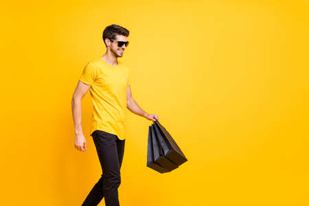 Photo of handsome guy holding boutique bags making abroad shopping going down fashionable mall floor wear casual t-shirt pants isolated yellow color background