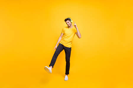 Full length photo of handsome guy at students party listening youth music, earflaps dancing youngster moves wear casual t-shirt pants isolated yellow color background
