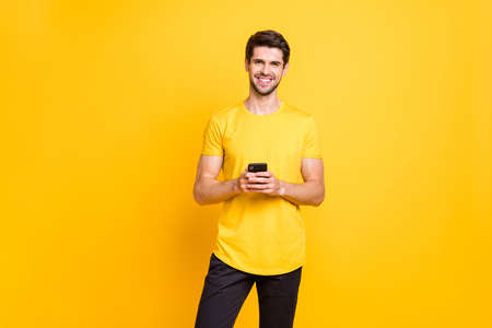 Photo of toothy cheerful cute attractive handsome man influencing people via his telephone by posting in social media pages isolated over yellow vibrant color background