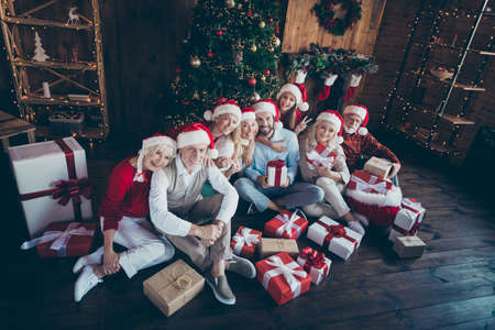 Top above high angle view photo of cheerful family with granddaughter showing v-sign surrounded with wrapped boxed sitting on floor under fir tree