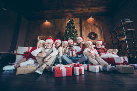 Photo of cheerful positive big family surrounded with gift boxed smiling toothily in front of christmas tree lights wreath in santa hat cap showing thumb up Zdjęcie Seryjne
