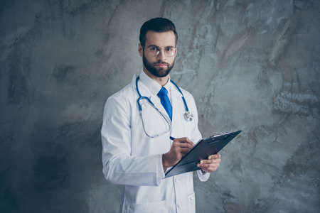 Portrait of concentrated doctor guy hold his clipboard write patients complaints wear white medical coat isolated over grey color background 写真素材