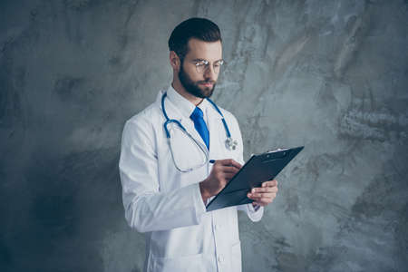 Profile side photo of focused surgeon man hear patients complaints write in his clipboard wear white medical coat isolated over grey color background Stockfoto