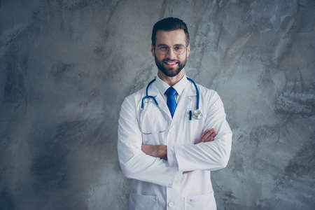 Portrait of positive cheerful bearded doctor successful medical worker concept cross hands ready to cure sickness wear white uniform isolated over grey color background