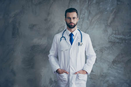 Portrait of serious talented doctor put his hands in pockets of white coat look ready to cure patients in clinic isolated over grey color background