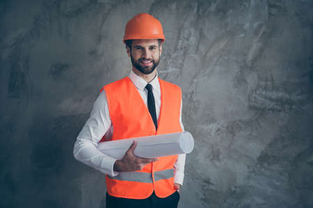 Portrait of positive professional builder architecture holding his plan for constructing building wear orange helmet uniform isolated over grey color background