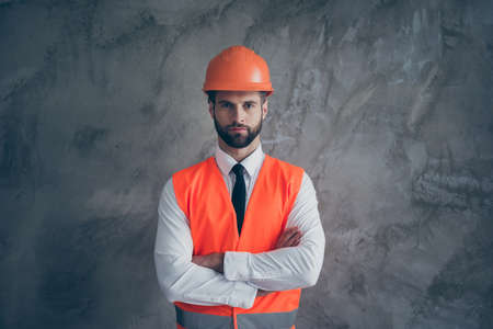 Portrait of confident cool builder cross hands ready to build great building house wear orange uniform with white shirt black tie isolated over grey color background 写真素材