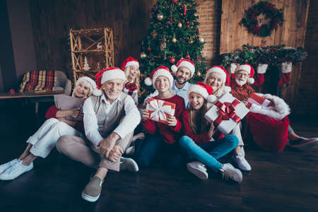 Photo of friendly big large family smiling toothily having new year party together sitting on floor in santa cap headwear children in childhood in front of decorated tree Zdjęcie Seryjne
