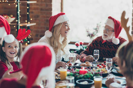 Photo of cheerful positive nice cute big family talking to each other while eating festive food with girlfriend antlered and everyone in santa hat at table Zdjęcie Seryjne