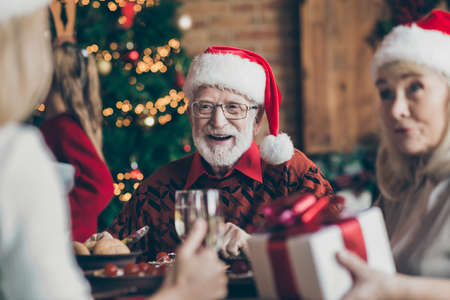Phot of grandfather positive cheerful smiling in eye glasses spectacles wearing santa hat headwear feeling festive mood in conversation with guests Stock fotó