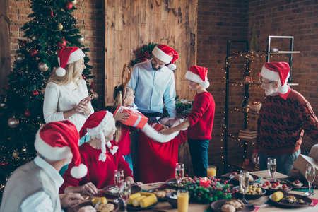 Photo of cheerful positive large family with father gifting presents to brother and sister small smiling toothily several generations meeting in santa caps Zdjęcie Seryjne