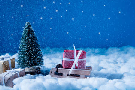 Photo of small wooden toy sledge, coming to santa claus place workshop in iceland loaded big red giftbox newyear snowy evening miracle magic concept