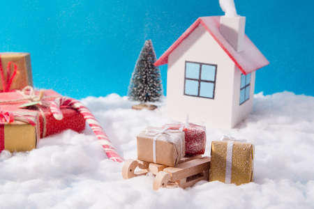 Small toy santa claus white comfort cozy warm house with smoke concept, deliver red brown giftboxes on wooden sledges standing under blue sky background