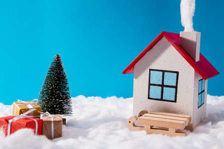 Small toy santa claus comfy house standing on north-pole with red brown giftboxes wood sledges fir tree under blue sky background