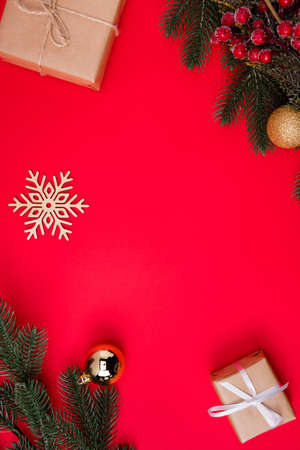 Vertical top above high angle view photo of empty space among snowflake, gifts and fir branches with christmas toys isolated red color vivid background