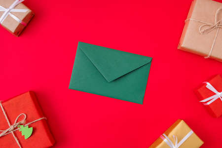 Top above high angle view photo of green envelope, lying among wrapped boxed isolated over vibrant color red background