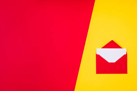 Photo of opened envelope with writted letter inside near empty space on red vivid color background, divided with yellow bright one