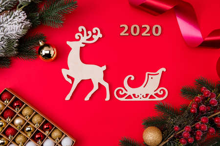 Top above high angle view photo of deer reindeer with sleigh behind surrounded, toys branches berries 2020 isolated bright red color background