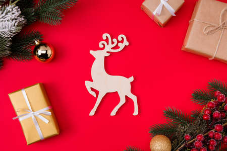 Top above high angle view photo of reindeer north deer surrounded with baubles branches of fir tree wrapped, packages isolated red color vibrant background