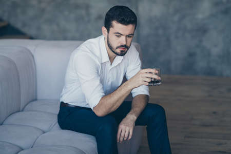 Portrait of his he nice attractive serious imposing bearded guy sitting on divan drinking beverage resting at modern industrial loft interior work place station indoors Reklamní fotografie