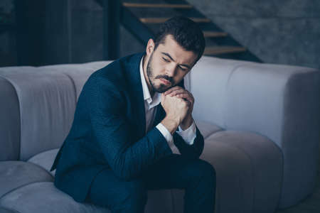 Portrait of his he nice rich imposing attractive luxury focused minded bearded guy wearing jacket sitting on divan thinking about problem solving in industrial interior room indoors
